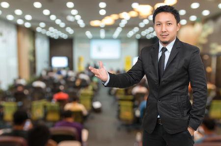 attendee: Asian Businessman with welcoming gesture on Abstract blurred photo of conference hall or seminar room with attendee background