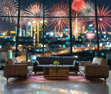 Lobby area of a hotel which can see Fantastic festive new years colorful fireworks on cityscape blurred photo bokeh in celebration night Stockfoto