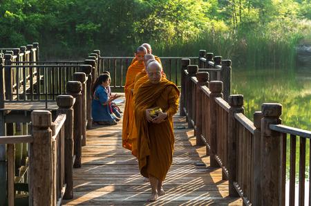 limosna: Nakhon Ratchasima, Tailandia - 31 de octubre: La gente no definidas se prepara el alimento para limosnas a los monjes budistas en pasarela de madera on octubre 31,2015 en Nakhon Ratchasima, Tailandia.