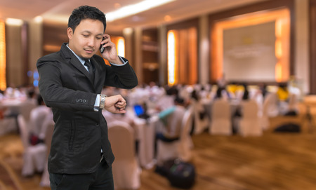 attendee: Young businessman talking on mobile phone and looking at watch on Abstract blurred photo of conference hall or seminar room with attendee background, business concept Stock Photo