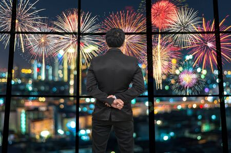 celebrate year: Back side of Businessman looking at Fantastic fireworks on the photo blurred of cityscape at night scene background,Business and holiday concept Stock Photo