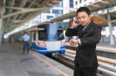 businessman waiting call: Young businessman talking on mobile phone and looking at watch on abstract Blurred photo of sky train at station with security guard, business rush hour concept Stock Photo