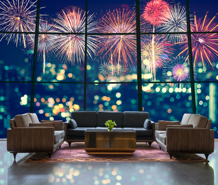 luxury lifestyle: Lobby area of a hotel which can see Fantastic festive new years colorful fireworks on cityscape blurred photo bokeh in celebration night Editorial