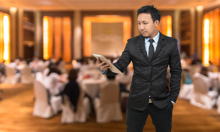 attendee: Asian Businessman looking the tablet on Abstract blurred photo of conference hall or seminar room with attendee background, business concept