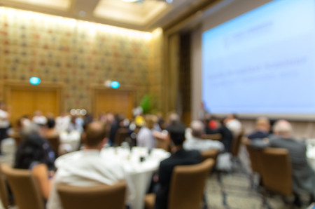 attendee: Abstract blurred photo of conference hall or seminar room with attendee background