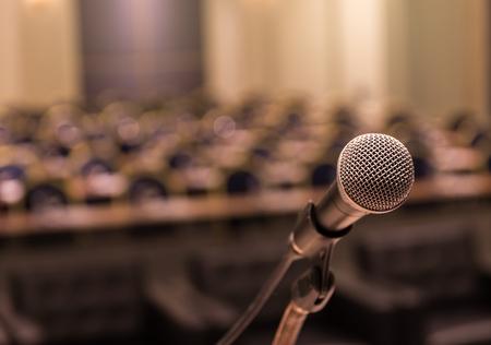 会議ホールやセミナー ルームの背景の抽象のぼやけた写真の上マイク