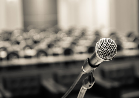 speaking: Microphone over the Abstract blurred photo of conference hall or seminar room background