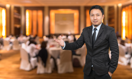 attendee: Businessman with welcoming gesture on Abstract blurred photo of conference hall or seminar room with attendee background, business concept