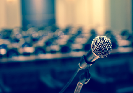 podium: Microphone over the Abstract blurred photo of conference hall or seminar room background
