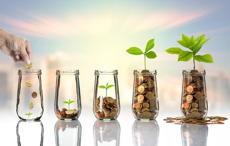 financial metaphor: Hand putting Gold coins and seed in clear bottle on cityscape photo blurred cityscape background,Business investment growth concept