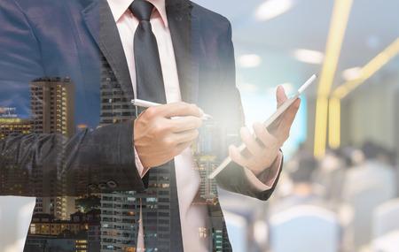 exposicion: Doble exposición de negocios usando la tableta en la foto borrosa abstracta de la sala de conferencias o sala de reuniones con el fondo de los asistentes Foto de archivo