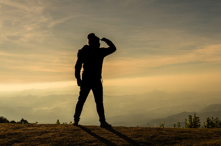 looking at: silhouette of a man who looking over the mountains landscape