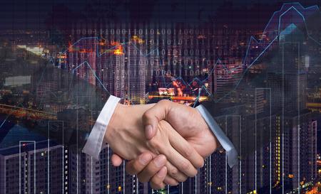 comercio: Sacudida de la mano entre el empresario en el gráfico de comercio en el paisaje urbano en el fondo del mapa del mundo y de la noche, concepto financiero de negocios