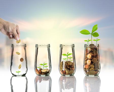 都市景観写真ぼやけて景観背景、ビジネス投資成長概念上明確なボトルにゴールド コインと種子を置く手