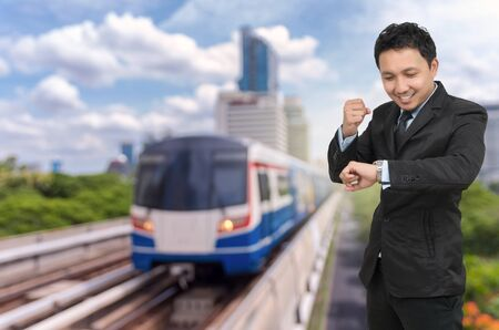 businessman waiting call: Young businessman looking at watch which cheerful action on abstract Blurred photo of sky train with traffic and cityscape, business rush hour concept