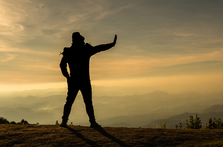 rejecting: silhouette of a man who show hand reject over the mountains landscape