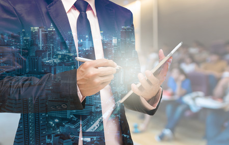 Double exposure of Businessman using the tablet on the Abstract blurred photo of conference hall or seminar room with attendee background Foto de archivo