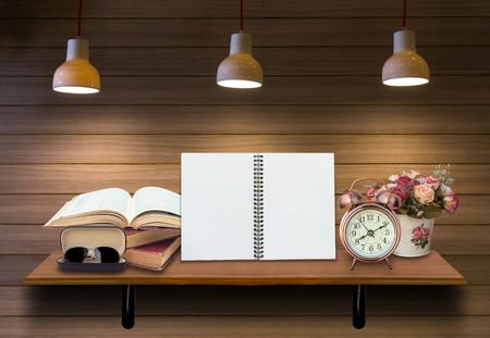 lighten: Top wooden shelves with empty netobook with open books, alarm clock and glasseson on the wooden wall background with lighten .Product presentation concept Stock Photo