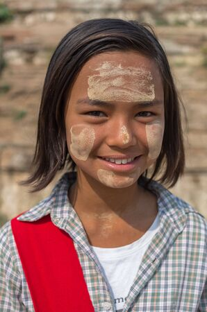 thanaka: MANDALAY, MYANMAR - MARCH 12 : Unidentified Burmese girl with traditional thanaka on her face on March 12, 2016 in Mandalay, Myanmar.Thanaka is a yellowish-white cosmetic paste made from ground bark Editorial
