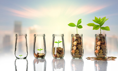 Gold coins and seed in clear bottle on cityscape photo blurred cityscape background,Business investment growth concept