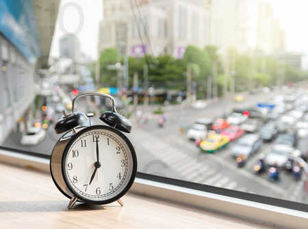 Vintage alarm clock at windows with abstract Blurred photo of traffic jam with rush hour on early morning, traffic tranportation concept Stock Photo