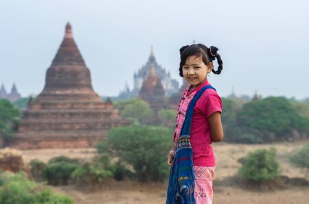 thanaka: Burmese girl with traditional thanaka on her face praying on pagoda blurred background at bagan in Mandalay, Myanmar Stock Photo