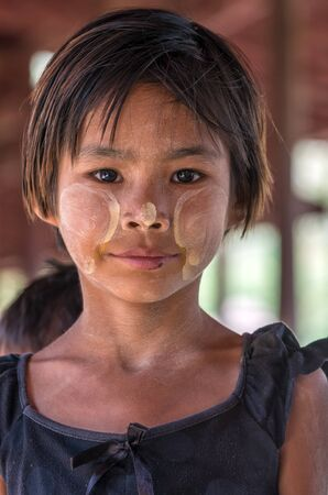 thanaka: MANDALAY, MYANMAR - MARCH 10 : Unidentified Burmese girl with traditional thanaka on her face on March 10, 2016 in Mandalay, Myanmar.Thanaka is a yellowish-white cosmetic paste made from ground bark Editorial