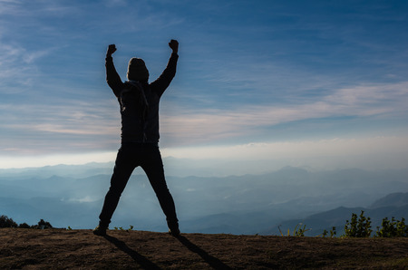 show of hands: silhouette of a man who show hands over the mountains landscape