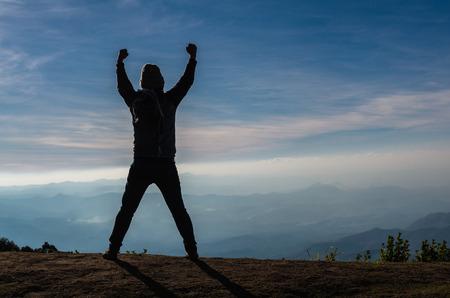 alzando la mano: silueta de un hombre que muestra las manos sobre el paisaje de montañas