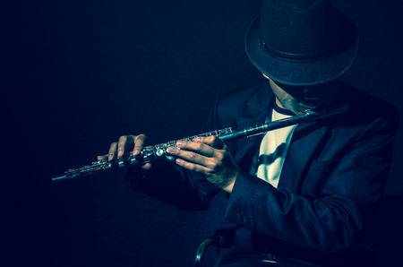 Flute music playing flutist musician performer on black background, musical instrument Stock Photo