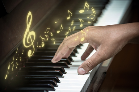 ivories: hands playing the piano with music notes,musical instrument Stock Photo