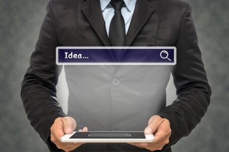 url virtual: Businessman holding the tablet with browsing of Internet searching %u201CIdea%u201D bar on the wall background Stock Photo