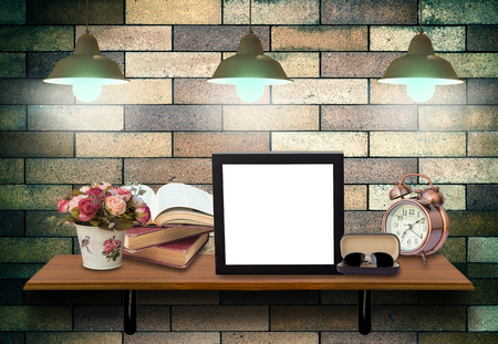 lighten: Top wooden shelves with Photo frame, books, alarm clock and glasseson on the brick wall background with lighten .Product presentation concept