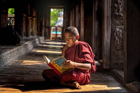 novice: Buddhist novice reading at Shwenandaw pagoda, mandalay, myanmar