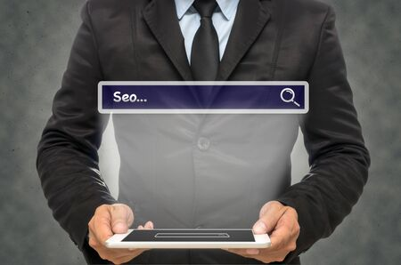 url virtual: Businessman holding the tablet with browsing of Internet searching �Seo� bar on the wall background, Internet concept