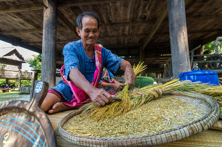 villager: NAKHON RATCHASIMA, THAILAND - OCTOBER 31: Undefined senior villager Making shredded rice grain which is traditional thai food at Beneath of the house on October 31,2015 in Nakhon ratchasima, Thailand.