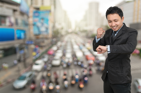 businessman waiting call: Young businessman looking at watch which cheerful action on abstract Blurred photo of traffic jam with rush hour, business rush hour concept