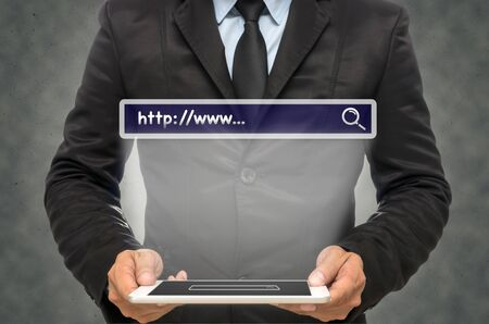 url virtual: Businessman holding the tablet with browsing of Internet searching �http:www�� bar on the wall background, Internet concept Stock Photo