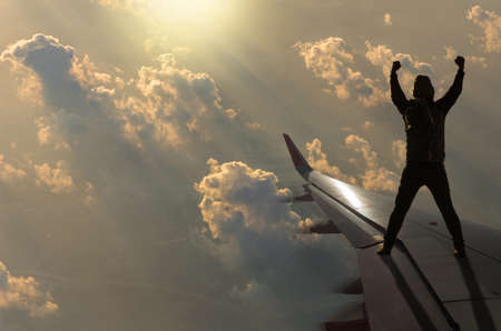 alzando la mano: silhouette of man who show hands over the sun with clouds on airplane wing, Challenge business concept Foto de archivo