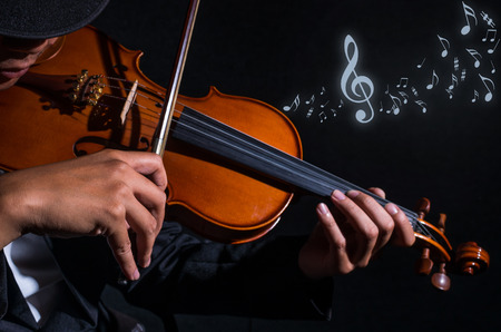 Close up Violin player in dark studio with music notes, Musical concept
