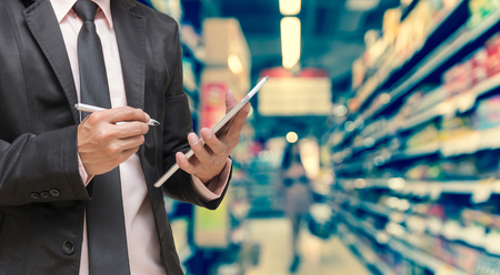 Businessman using the tablet on Abstract blurred photo of store in department store bokeh background, business shopping concept Standard-Bild