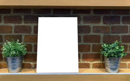 bill board: Empty bill board on the wooden shelves with fake flower on the brick wall background. Product presentation concept