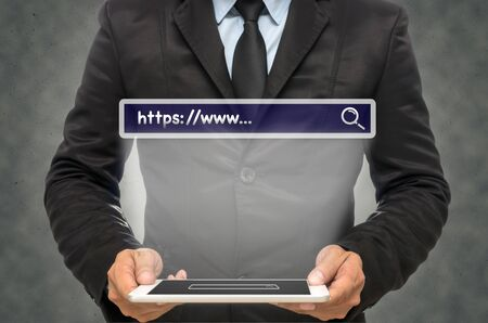 "url virtual: Businessman holding the tablet with browsing of Internet searching ""https:www…"" bar on the wall background, Internet concept"