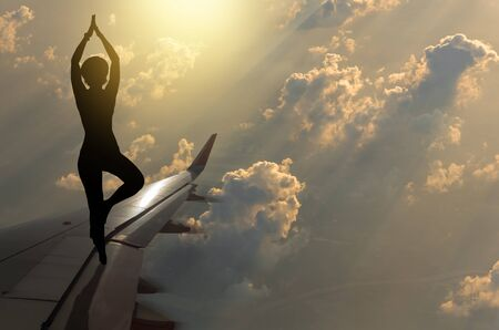 silhouette of yoka girl with the sun set with clouds on airplane wing, Challenge exercise concept Banco de Imagens