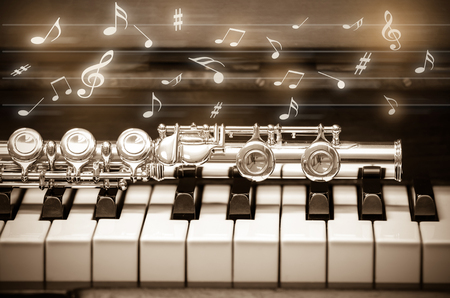 serenade: Closeup Flute on the keyboard of piano with music demody, musical instrument, vintage tone