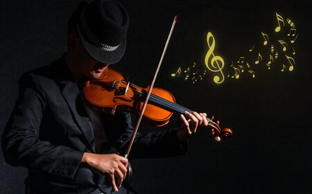 violin player: Violin player in dark studio with music notes, Musical concept