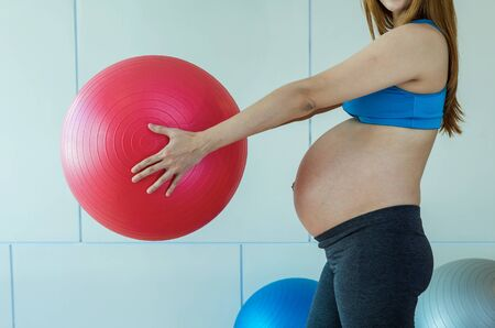 big ball: Closeup asian Pregnant female do exercise in sports room, holding the big ball, healthy motherhood concept