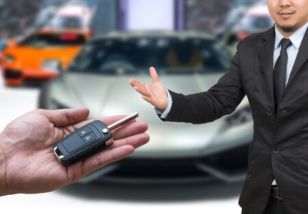 lock and key: Businessman with welcoming gesture and Man hand holding and giving a car key remote on photo blurred of car, transportation and ownership concept Stock Photo