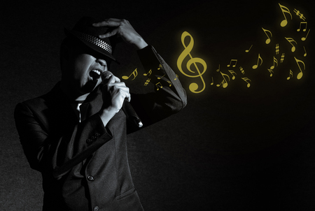 concert background: Songer hand holding the microphone and singing with music notes on black background, musical concept