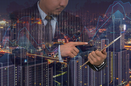 investment concept: Double exposure of businessman using the tablet with cityscape with trading graph on blurred building background, Business invest concept